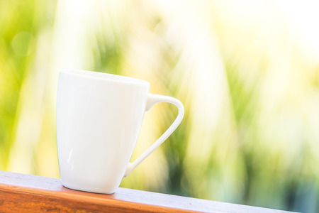 mug of coffee: White coffee cup with outdoor view background - sunflare filter