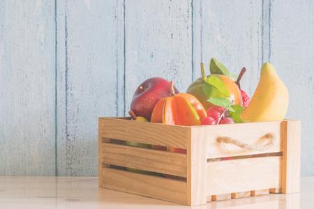fruits in a basket: Fruit basket on wood background - Vintage light tone filter processing