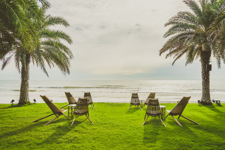 sharm: Wood chair on the green grass with beach and palm tree background - vintage filter