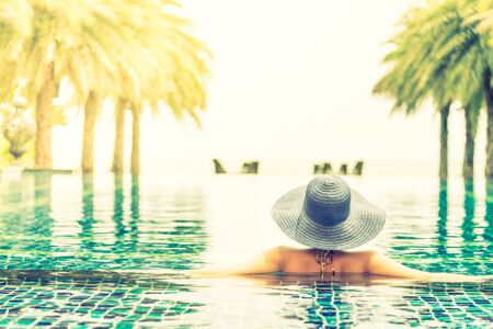 Young woman wearing straw hat in the pool - vintage filter Stock Photo