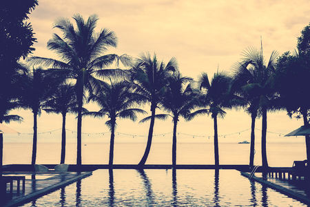 resort: Silhouette palm tree on the beach with swimming pool in hotel resort - vintage filter effect