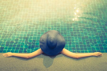 people relax: Woman in swimming pool - vintage filter and light leak effect processing
