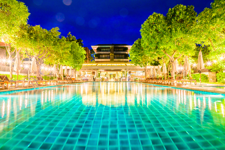 hotel resort: Swimming pool with palm trees in resort hotel at night - (Long speed shutter , The palm trees hit the wind blows)