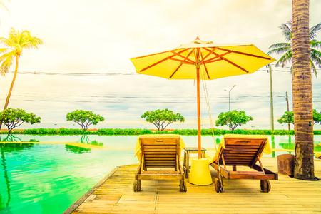 playas tropicales: Silla de paraguas en el hotel turístico de la piscina con la puesta del sol - filtro de la vendimia y sunflare procesamiento de filtro de luz