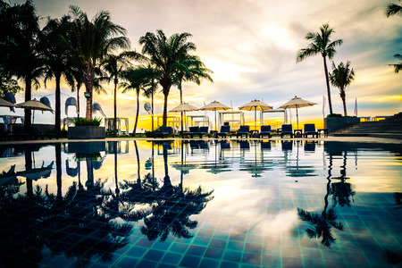 hotel resort: Silhouette palm trees with umbrella chairs in luxury hotel resort pool at sunrise times