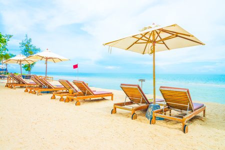 sunny beach: Umbrella and chair on beautiful tropical beach - summer vacation background Stock Photo