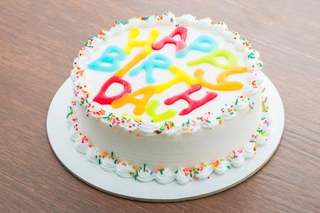 cream cakes: Happy birthday cake on wooden background
