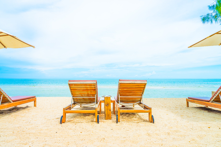 lounge chairs: Umbrella and chair on beautiful tropical beach - summer vacation background Stock Photo