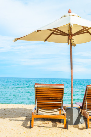 beach umbrella: Umbrella and beach chair with beautiful tropical beach - summer vacation background Stock Photo