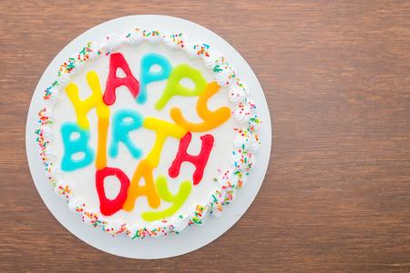 happy birthday text: Happy birthday cake on wooden background