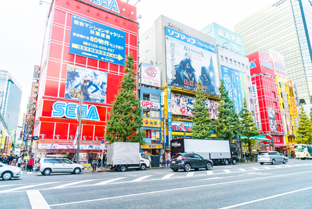business game: TOKYO, JAPAN - November 26, 2015: Crowded people traffic passes with colorful signs at Akihabara. The electronics and Toys district in Tokyo Japan.