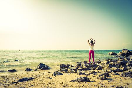 siluetas mujeres: La acción de la mujer joven de la yoga en la playa - efecto vintage y el proceso de filtro de la flama del sol Foto de archivo