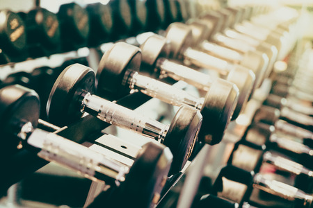 Selective focus point on Dumbbell in fitness and gym room interior - Vintage filter effect Stockfoto