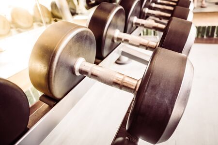 heavy effect: Soft focus point Dumbbell equipment in fitness gym room - Vintage Filter