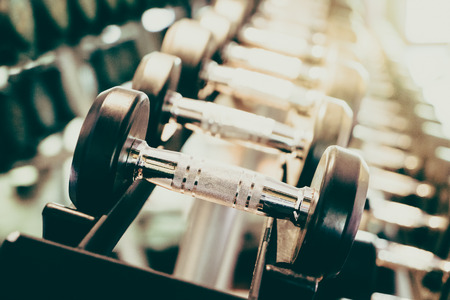gym equipment: Selective focus point on Dumbbell in fitness and gym room interior - Vintage filter effect Stock Photo
