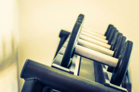 weight training: Selective focus point on Dumbbell equipment in fitness gym - Vintage filter