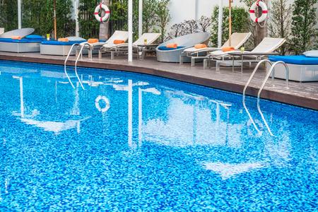 hotel resort: Umbrella and chair around beautiful luxury swimming pool in hotel resort Stock Photo