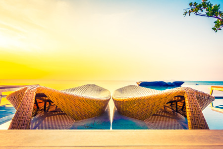 resort: Beautiful luxury hotel swimming pool resort with umbrella and chair on the beach and sea - Vintage Filter and Boost up color Processing