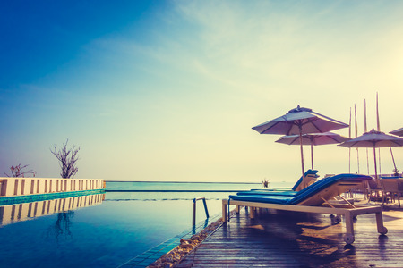 resort beach: Beautiful luxury swimming pool in hotel resort with umbrella and chair in sunset times - Vintage Filter and Boost up color processing Stock Photo