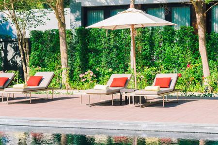 Sombrilla y silla en complejo de piscina de hotel de lujo hermoso - Imágenes de estilo de procesamiento de filtro