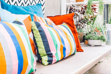 Patio outdoor deck with colorful pillow on chair decoration exterior of home - Vintage light filter Archivio Fotografico