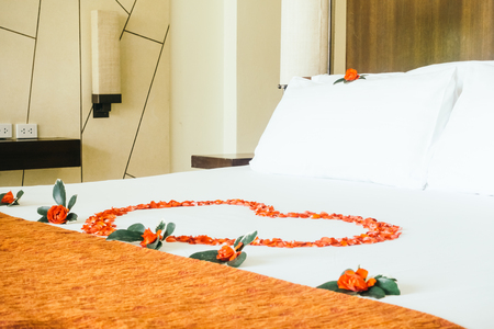 honeymoon suite: Honeymoon bed decoration with swan towel with rose flower decoration in bedroom interior - Vintage Light Filter