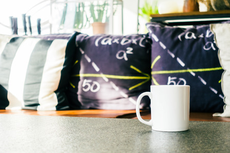 mug of coffee: White coffee cup on table with sofa pillow decoration interior of living room - Vintage Light Filter Stock Photo