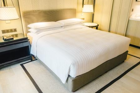 Oreiller blanc de luxe magnifique sur le lit et lampe sur la décoration murale dans l'intérieur de la chambre - Vintage Light Filter Banque d'images