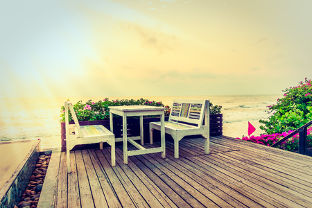 adirondack: Empty table and chair on the beach background - Vintage filter and Sunflare effect Stock Photo