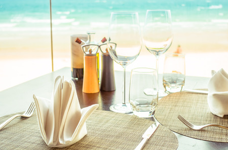 table: Selective focus point at Table setting for dinner with wine glass and etc in restaurant - Vintage Light filter