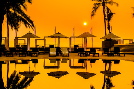 el sheikh: Beautiful Silhouette palm tree with umbrella and chair around luxury swimming pool in hotel resort at sunset time - Vintage Filter and Color boost Up Processing