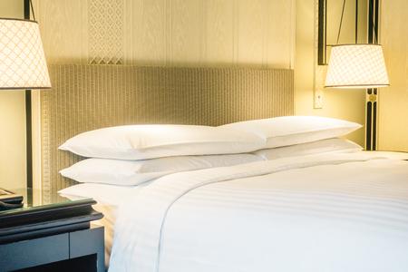 침대와 침실 인테리어 벽 장식 조명 램프에 아름 다운 흰색 럭셔리 베개 - 빈티지 라이트 필터