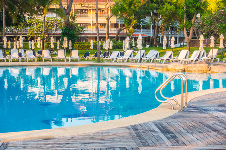 resort: Beautiful luxury outdoor swimming pool with umbrella and chair in hotel resort Editorial