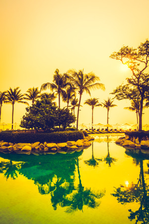 el sheikh: Beautiful Silhouette luxury umbrella and chair around swimming pool in hotel pool resort with coconut palm tree at sunrise times - Vintage Filter and Boost up color Processing