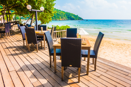 adirondack: Empty table and chair decoration outdoor restaurant with sea and beach background Stock Photo