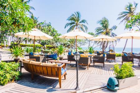 Outdoot patio met kussen op de bank en een stoel op het strand en de zee - Vintage Light Filter