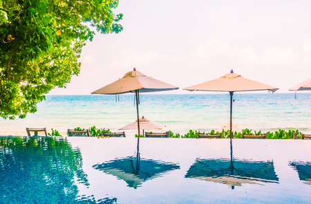 porch scene: Beautiful luxury Umbrella pool and chair around swimming pool neary beach and sea in hotel resort - Vintage Filter