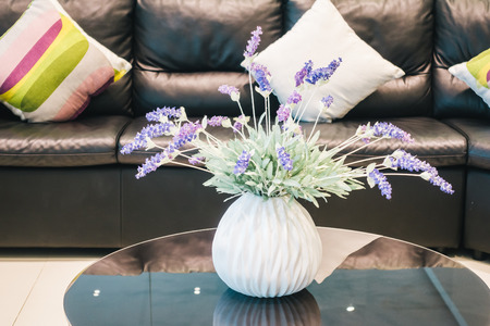 room decoration: Vase flower decoration in living room interior with pillow on sofa - Vintage light Filter Stock Photo