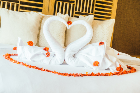 honeymoon suite: Swan towel and rose flower with beautiful luxury pillow decoration on bed in bedroom interior - Vintage light Filter