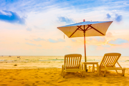Beautiful tropical beach and sea landscape with coconut palm tree and umbrella and chair - Vintage Filter Stock Photo
