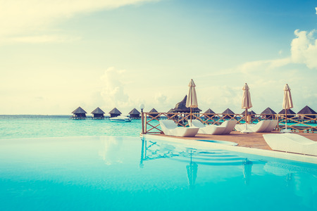 hotel resort: Beautiful luxury outdoor swimming pool with umbrella and chair in hotel resort at maldives - Boost up color and Filter effect Processing