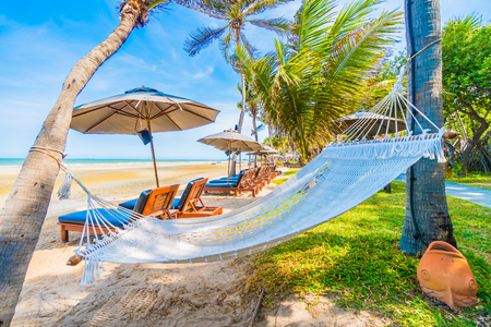 island paradise: Umbrella and chair on the beautiful tropical beach and sea with coconut palm tree - Boost up color processing