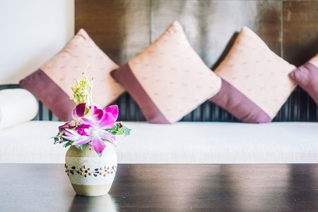selective focus: Selective focus point on vase flower decoration in living room area with pillow on sofa - Vintage light Filter Stock Photo