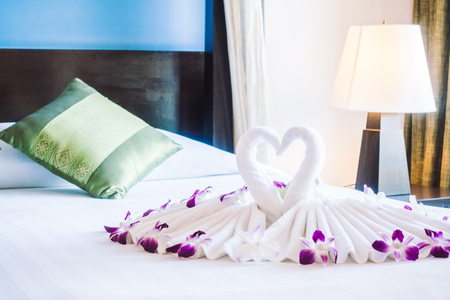 honeymoon suite: Romantic concept for background with Swan towel on bed decoration in bedroom interior - Vintage light Filter