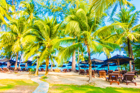 Umbrella and chair on the beautiful tropical beach and sea landscape with coconut palm tree - Boost up color Processing