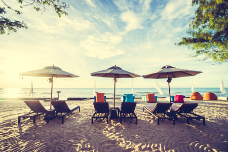 desolated: Outdoor with umbrella and chair on beautiful tropical beach and sea at Sunset time - Vintage Filter Stock Photo