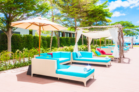 hotel resort: Umbrella and chair around swimming pool in beautiful luxury hotel resort for holiday vacation concept background Stock Photo