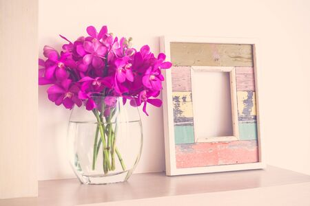Alter hölzerner Fotorahmen mit Orchideenblume im Vasendekorationsinnenraum des Raumes - Weinlese-Filter Standard-Bild