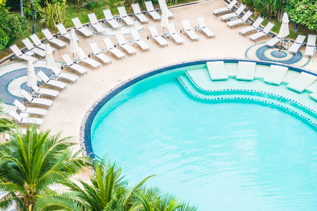 hotel resort: Outdoor swimming pool with umbrella and chair in hotel resort Editorial
