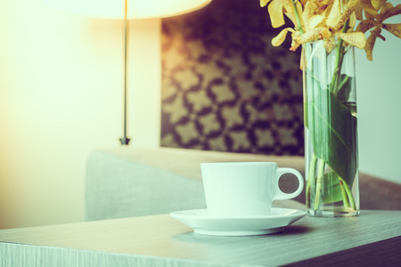 living wisdom: White coffee cup on wooden table with vase flower decoration interior of room - Vintage Filter